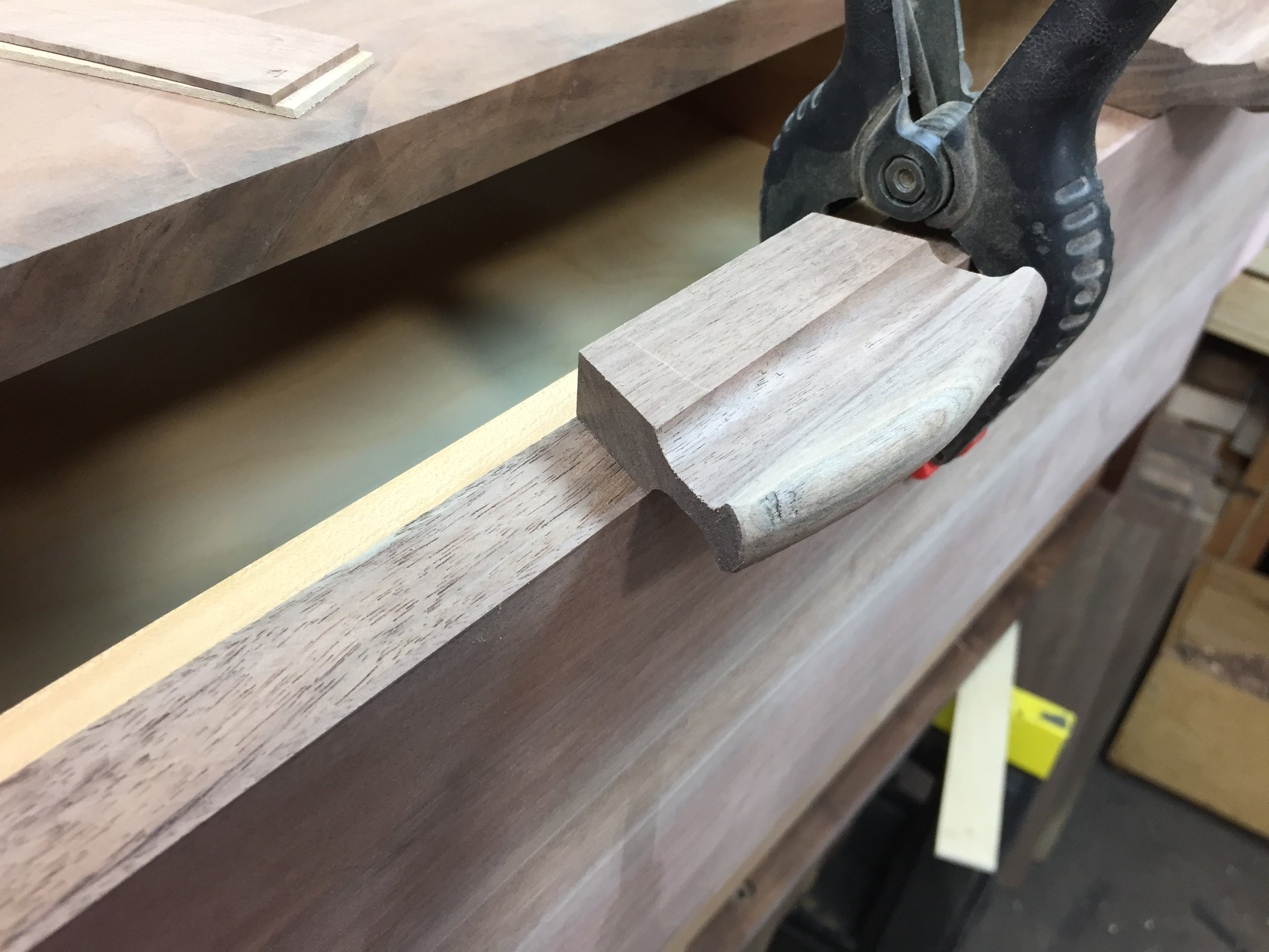 Rough shape positioned on the top edge of a drawer front