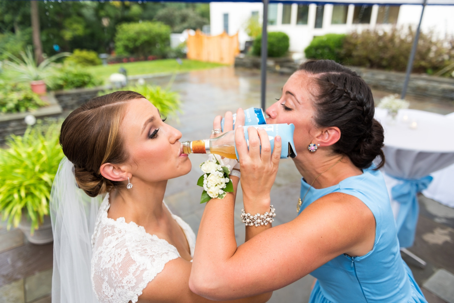 The bride chugs with her maid of honor.