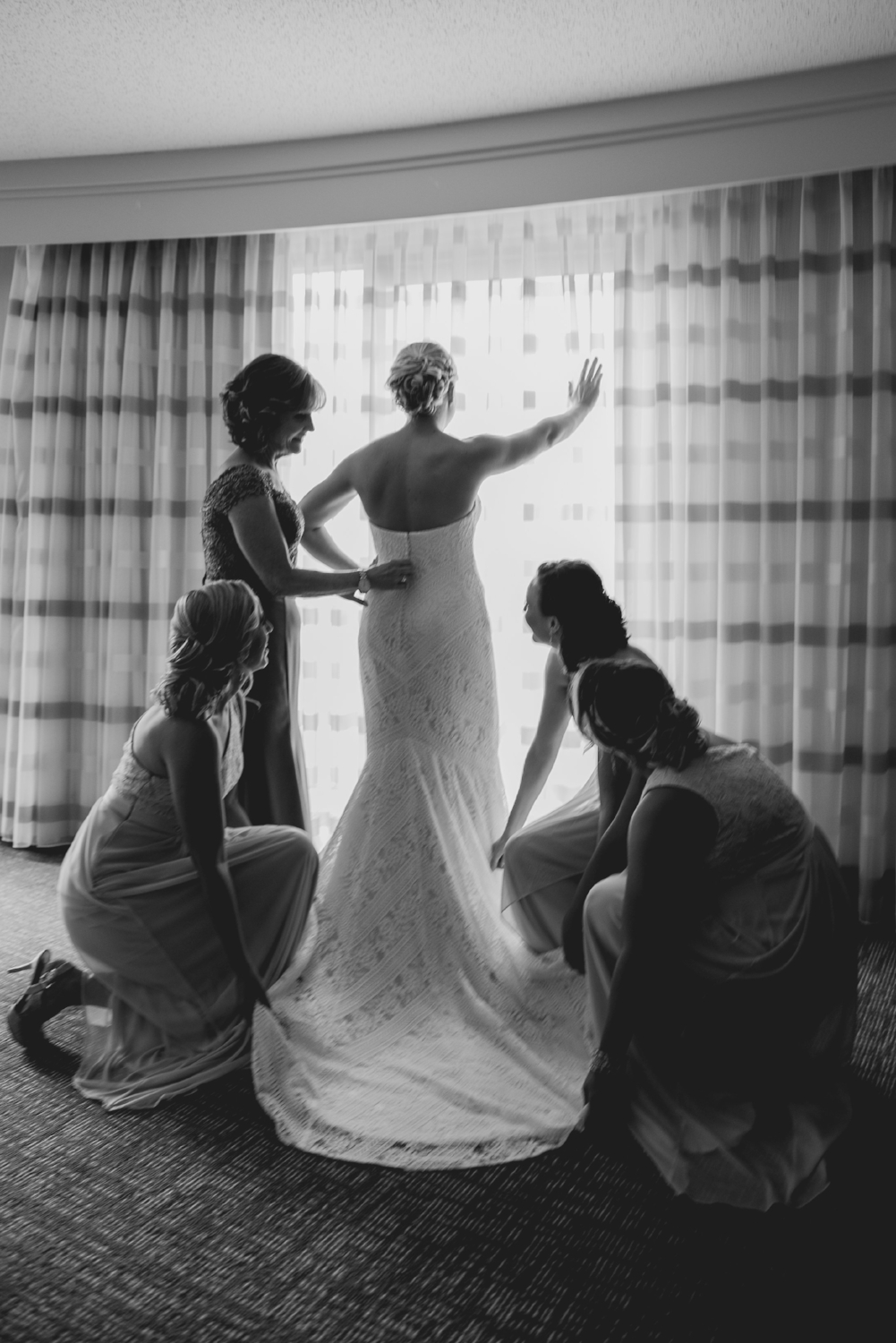 mother-of-bride-and-bridesmaids-help-bride-with-dress
