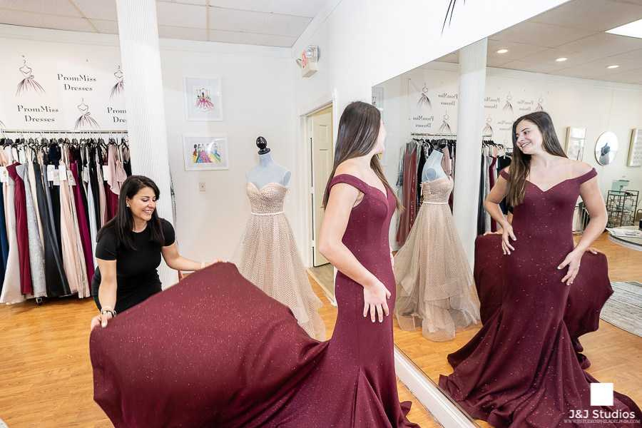 Dina helps a client try on her dress at prommiss dresses