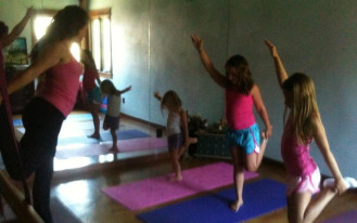 Lily leading a mixed age children's yoga class.