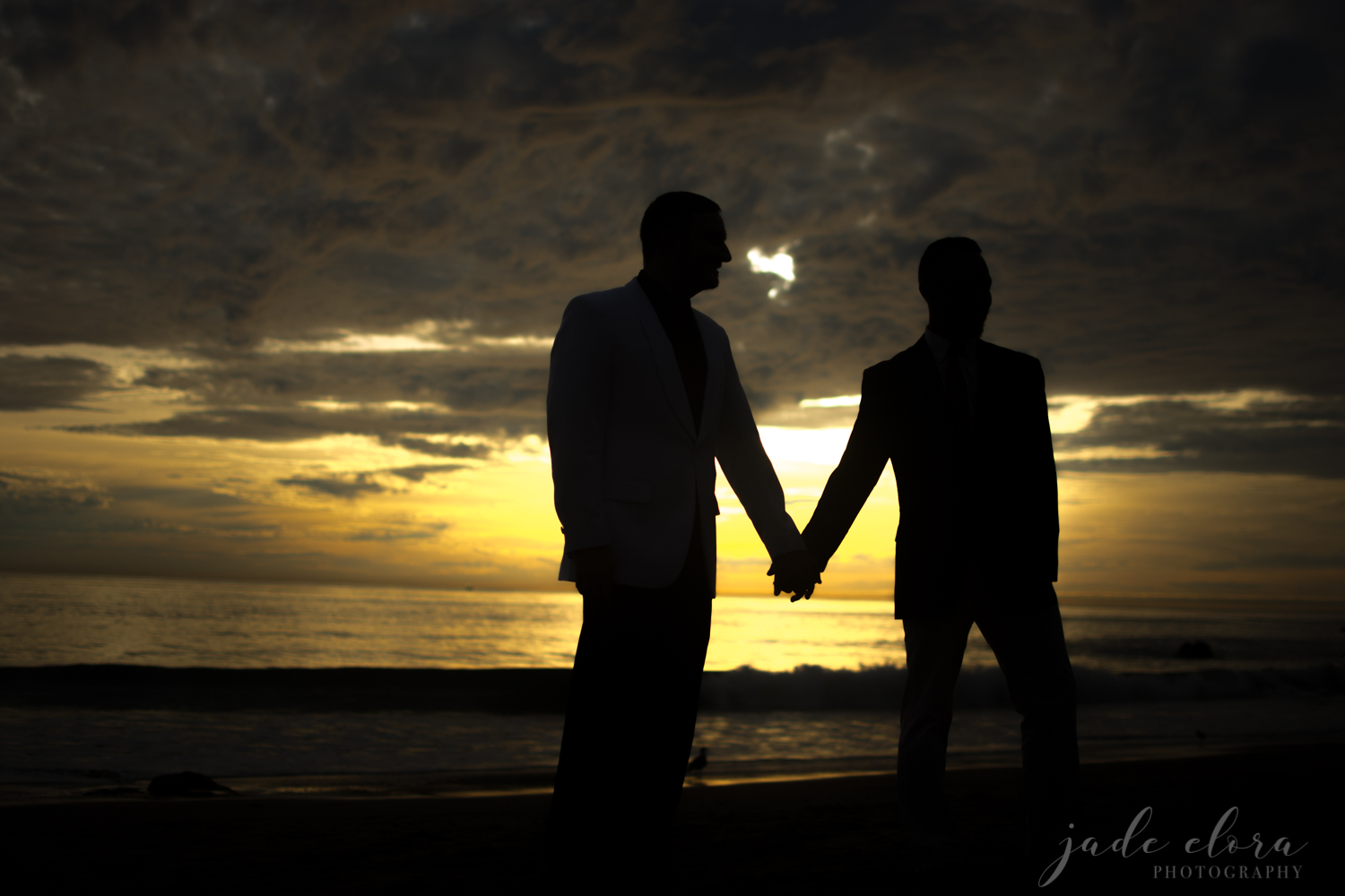 Two Male Silhouettes Holding Hands Against Sunset Backdrop