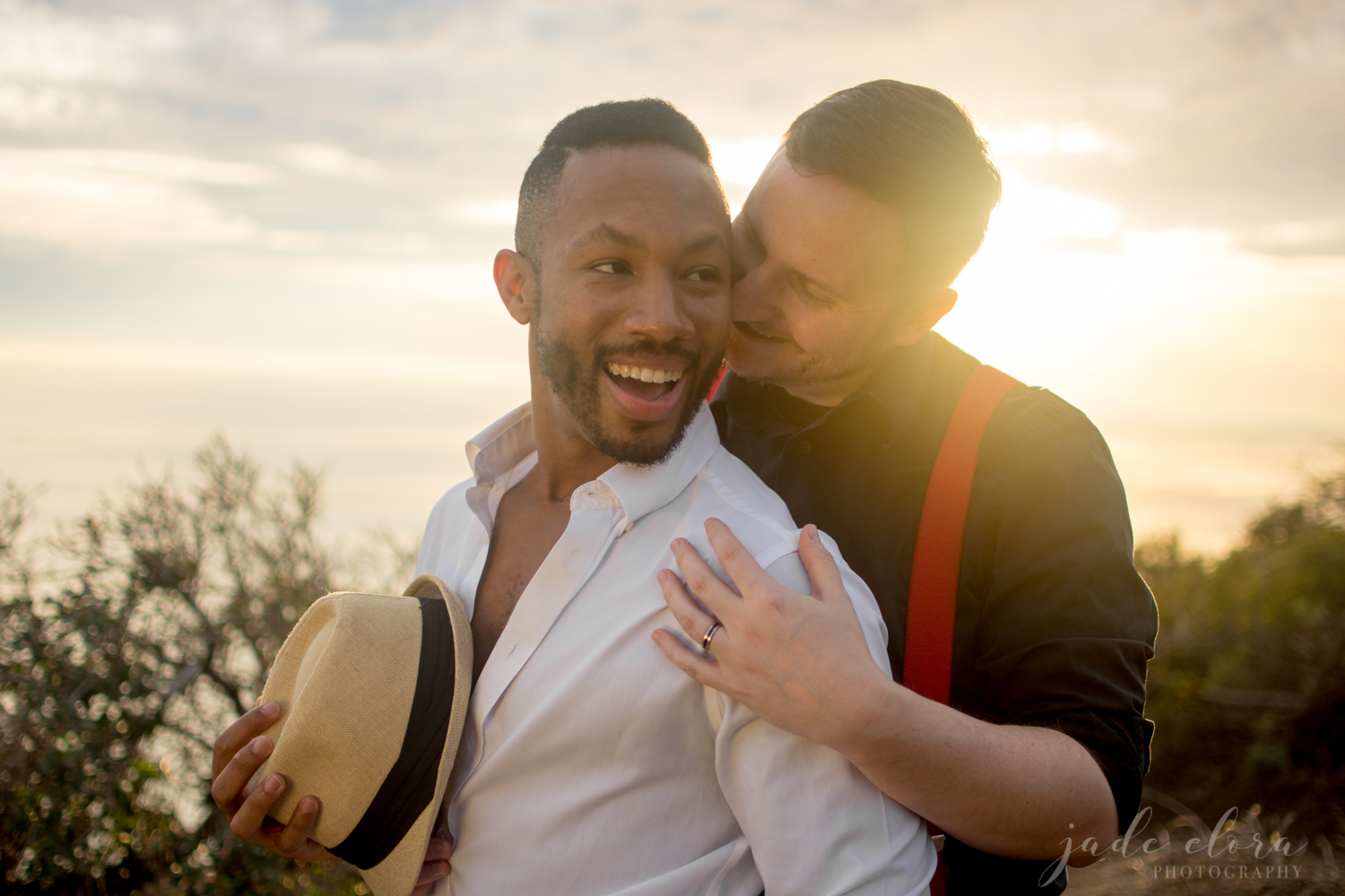 Same Sex Engaged Male Couple Hugs at Sunset
