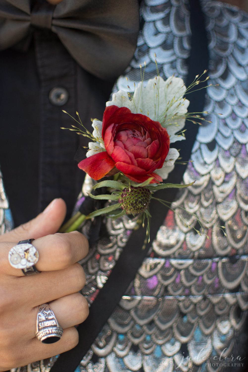 Close Up of Rock n Roll Groom's Hand On Red Boutonniere