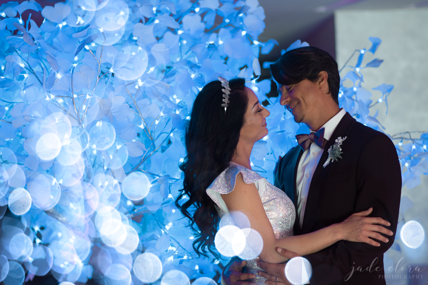 Couple Hugging Surrounded by Blue Lights in Front of Blue Lit Tree