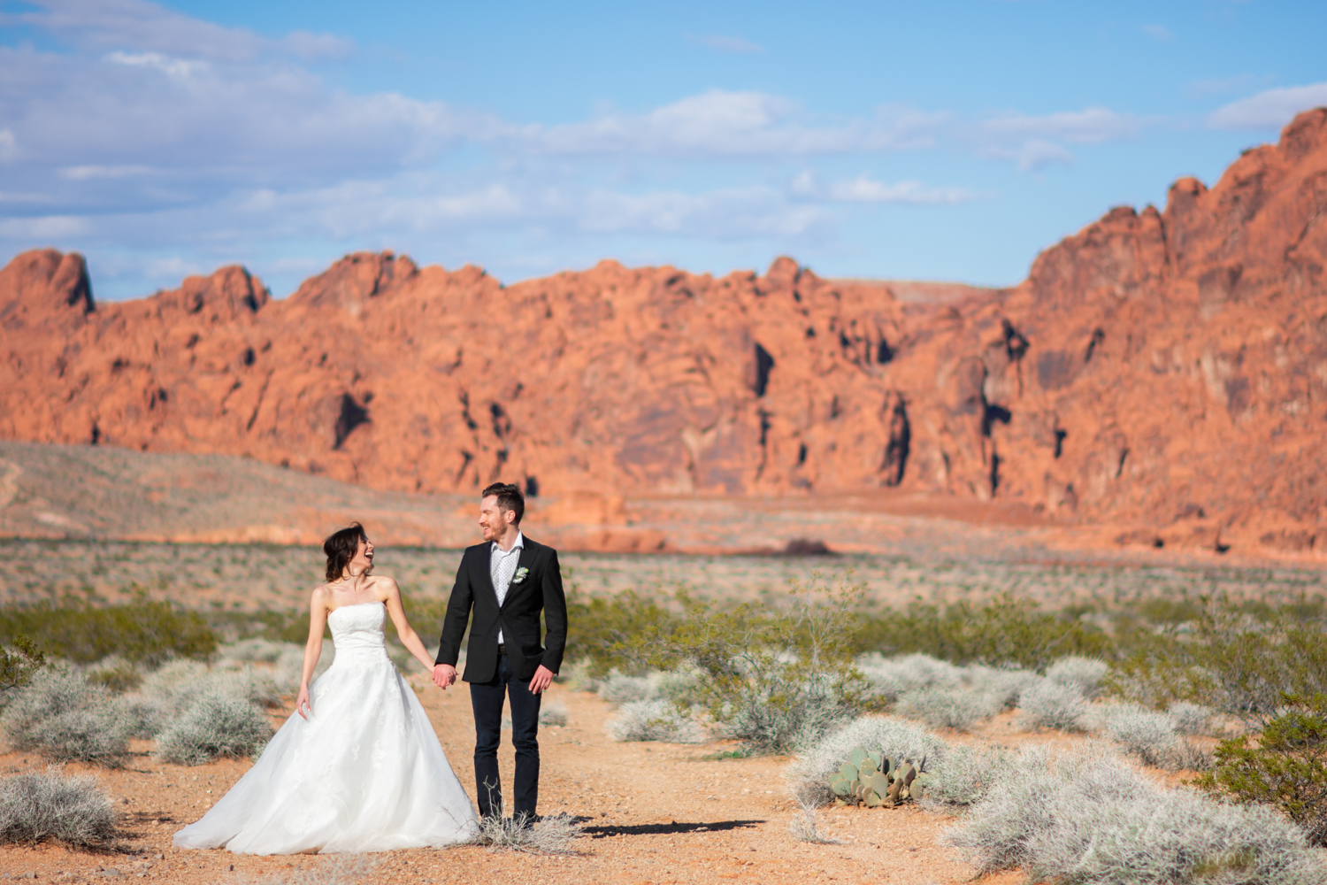 Couple in Wedding Attire Holding Hands and Laughing in the Desert