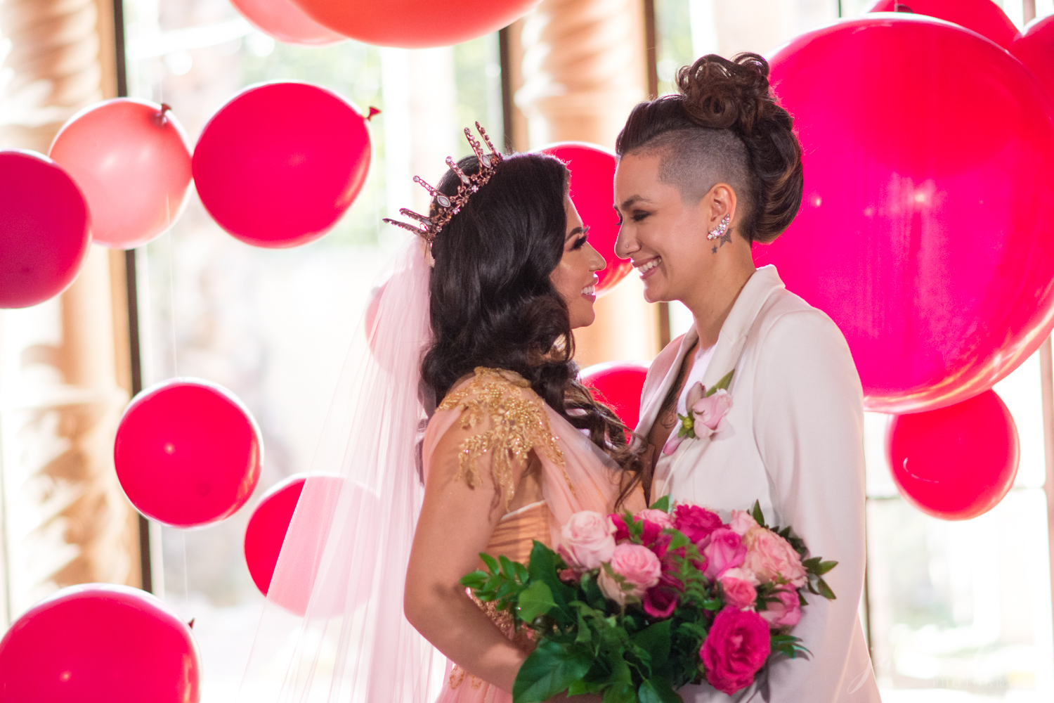 Lesbian Wedding Couple Laughing Surrounded by Red and Pink Balloons