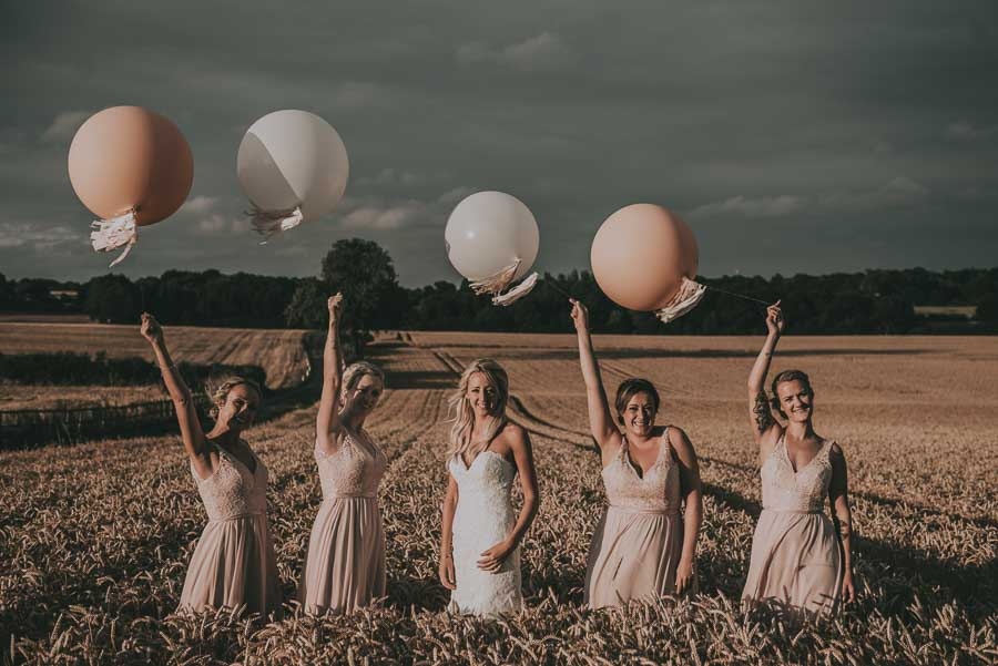 Bride and bridesmaids in field with balloons