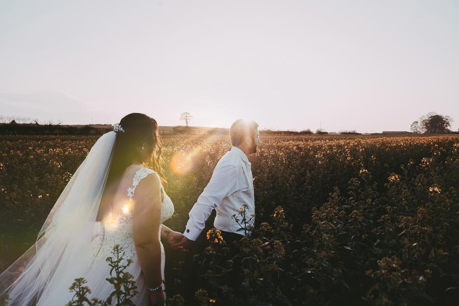 Bride and groom sunset field