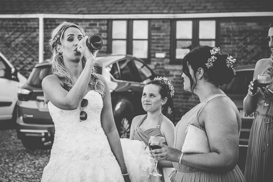 Bride drinking from a bottle of prosecco