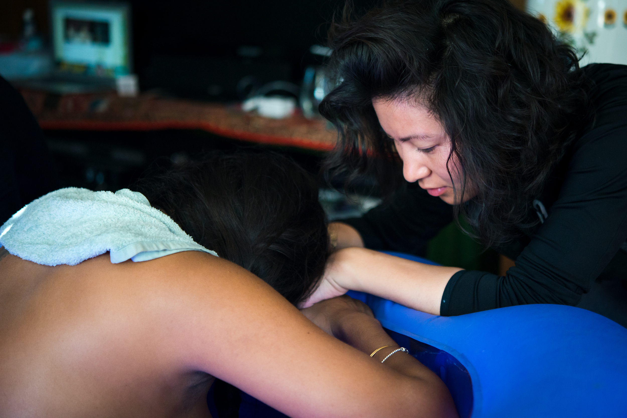 Doula Yien supports a mama having a natural delivery at home by keeping her calm, focused, and on top of her contractions. Yien provides continuous physical and emotional support until the baby is born, never leaving the mom's side.  Photo by Pam Ellis