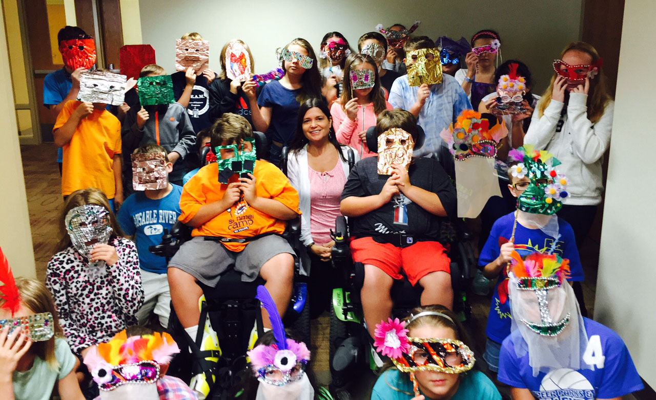 Sixth graders proudly displaying their mask creations. See the metal tooling mask making project lesson overview below.