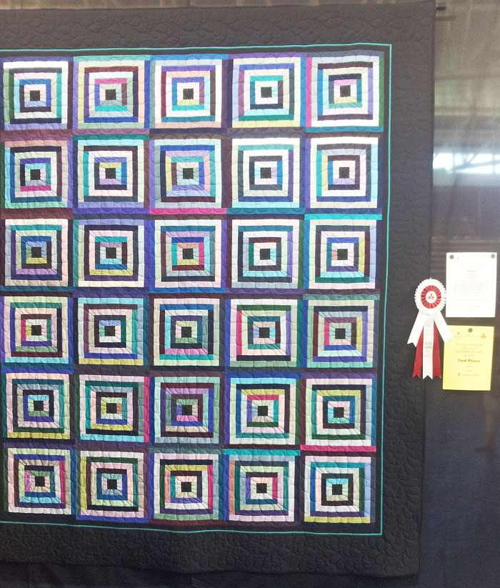 """Making Do  at the Canadian Quilter's Association's National Juried Show with a second place ribbon in the """"Original Interpreted Bed Quilt"""" category. I couldn't get to the show in Lethbridge, AB and asked a friend if she could take a picture for me. """"They"""" do not allow pictures in the NJS, strange because they publish a catalogue with all the pictures of all the quilts. I hope I don't get """"in trouble"""" for posting this picture but I am just so very pleased! I hope CQA will reconsider their policy for """"no photographs"""", I think it is time!"""