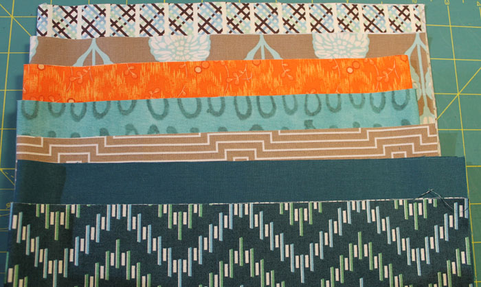 """The turquoise and orange fabrics were two I added. I eliminated a mustard yellow. The theme this year is Poetry and I have chose """"Stopping By The Woods on a Snowy Evening"""" by Robert Frost. I have also added a white fabric with silver metallic swirls. I have just started quilting it and will share pictures soon."""