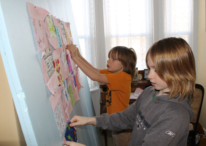 "Grandsons Evan and Ben have a new baby step-sister so we have been working on a quilt for her. It is the great ""Falling Charms"" pattern by Missouri Star Quilt Co. They have both been using the sewing machine, Evan just had to find out how fast it would go! He was surprised! It is all pieced now, just the borders to sew on then we can baste and quilt it. Yes, it is pink but there are firetrucks, dragons, fish, lobsters and sailboats! I have loved every minute working on this project with them."
