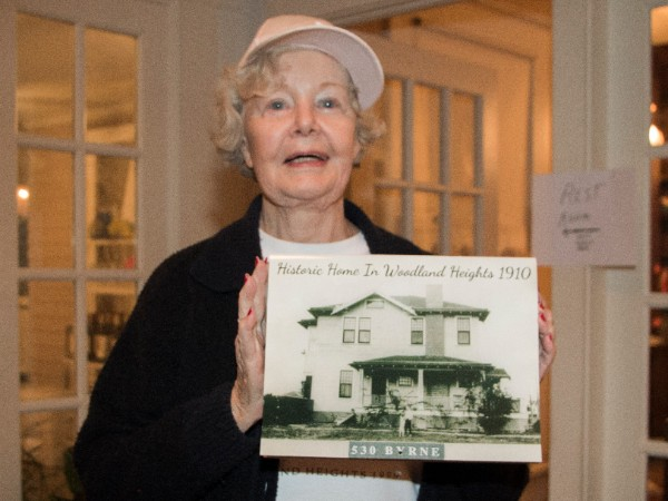 Janeen Cook offers a calendar containing photos of her family's historic Rolle House. The house has been in the family since it was built.