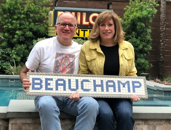 Pam & Greg Roach of 3304 Beauchamp with their new sign courtesy of the Blue Tiles Project.