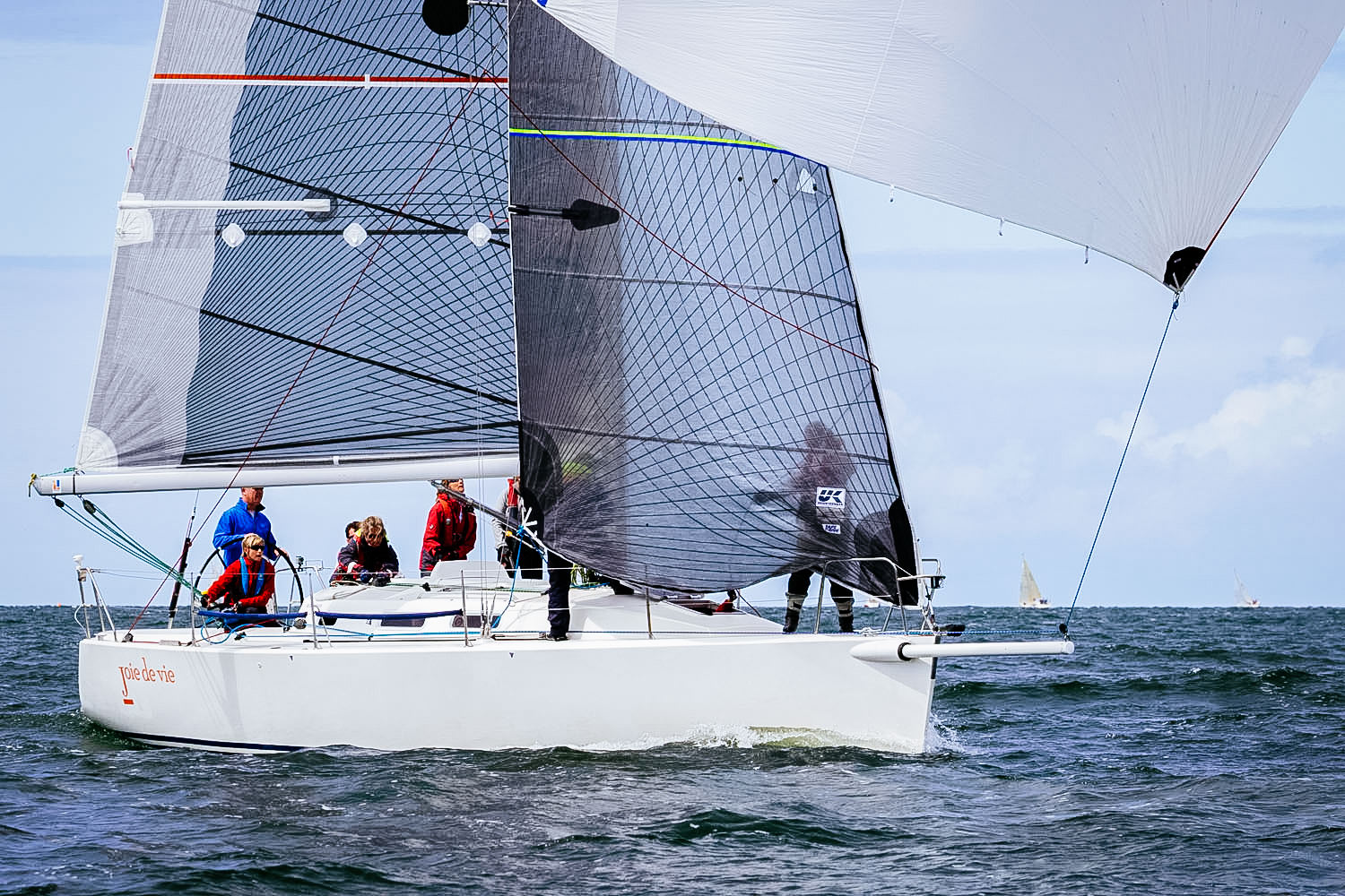 J/109 with Tape-Drive carbon and black aramid racing sails. The mainsail has a  one-meter  taffeta strip up the leech to increase the sail's longevity. Notice that the inboard edge of the taffeta has an optional wavy pattern instead of straight edge to reduce hinging.