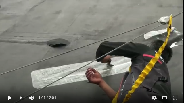 A Volvo 70 mainsail being patched with Dr. Sails while underway.