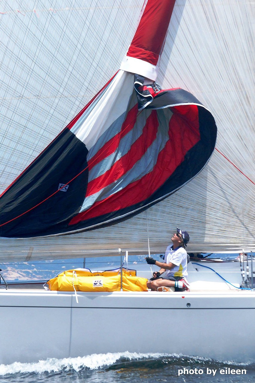 Once the Cruising Spinnaker is raised inside the sock, use the continuous loop halyard to raise the sock to the free the sail. When the cruising spinnaker is flying, the Stasher sits over the top of the sail as shown below.