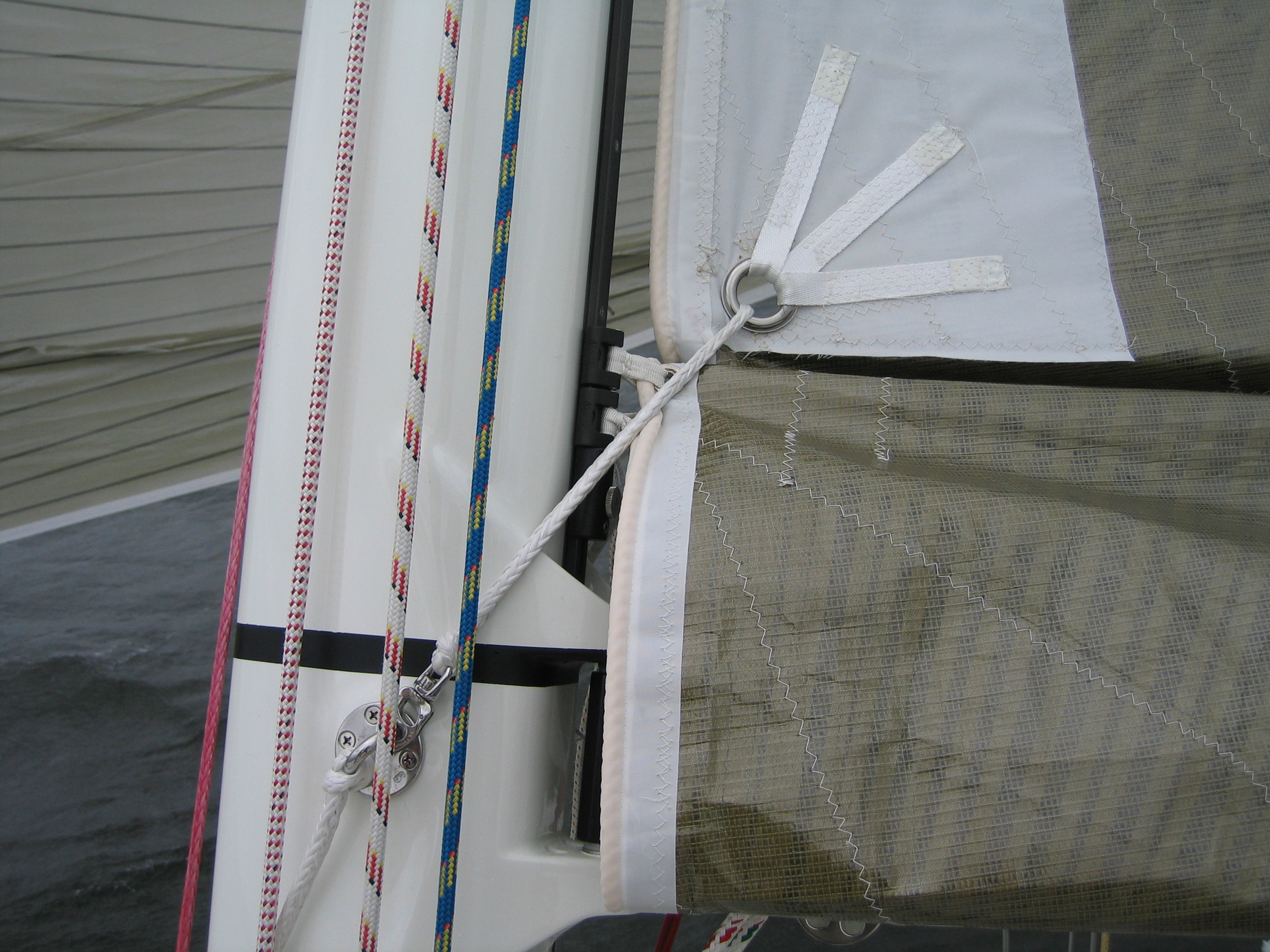 Photo 3 :The reef tack his held by the white Dyneema line that comes from a padeye on the far side of the mast, through the reef tack grommet where it snaps into place on the padeye located below the black measurement band.
