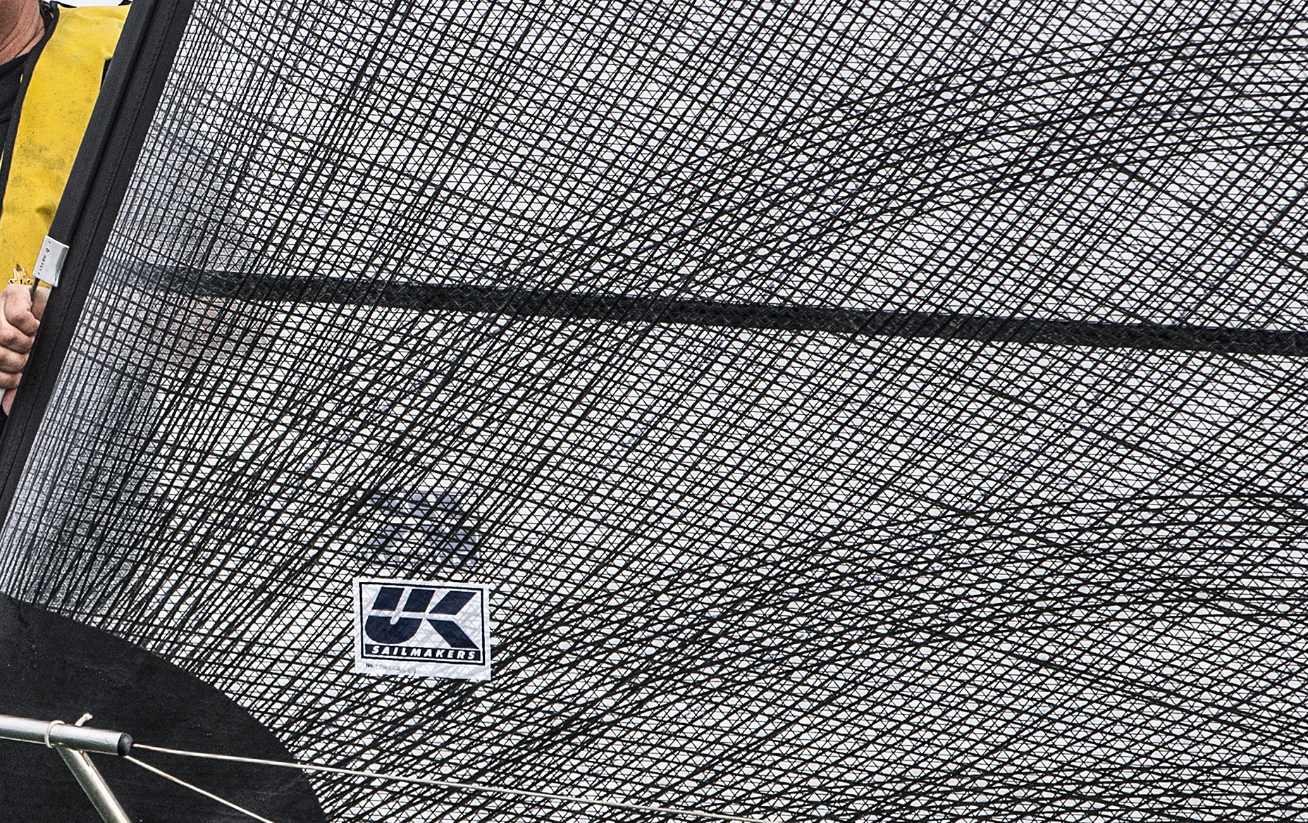 Close up of the carbon X-Drive fibers near the tack of a genoa. The dark horizontal line is the seam between panels. The X-Drive fibers are bonded to the sail across the seams, which prevents speed-killing seam-creep.