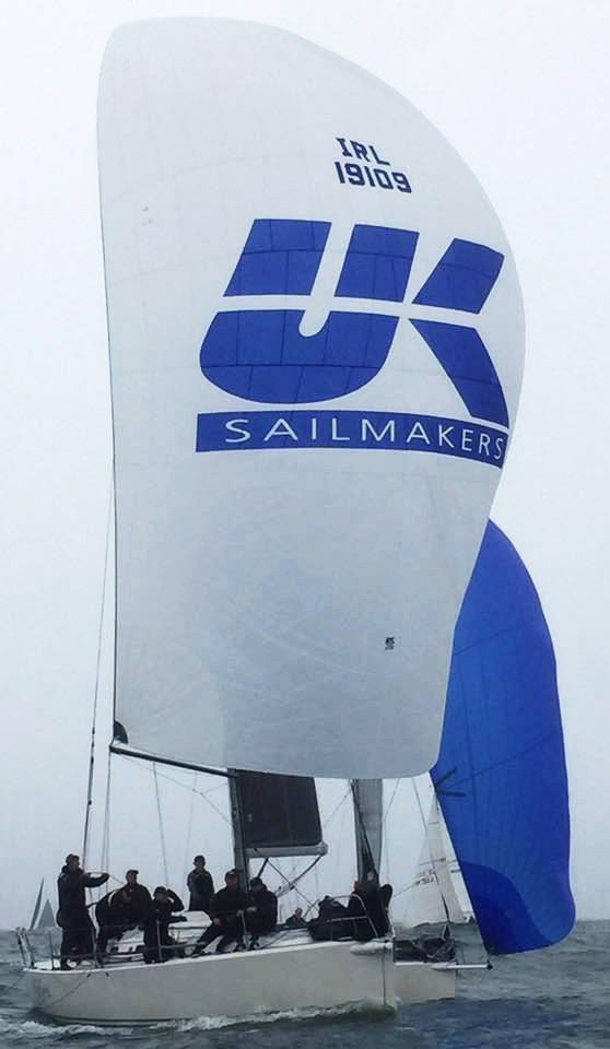 The J/109 OUTRAJEOUS sailing with her symmetrical spinnaker nearly dead downwind.