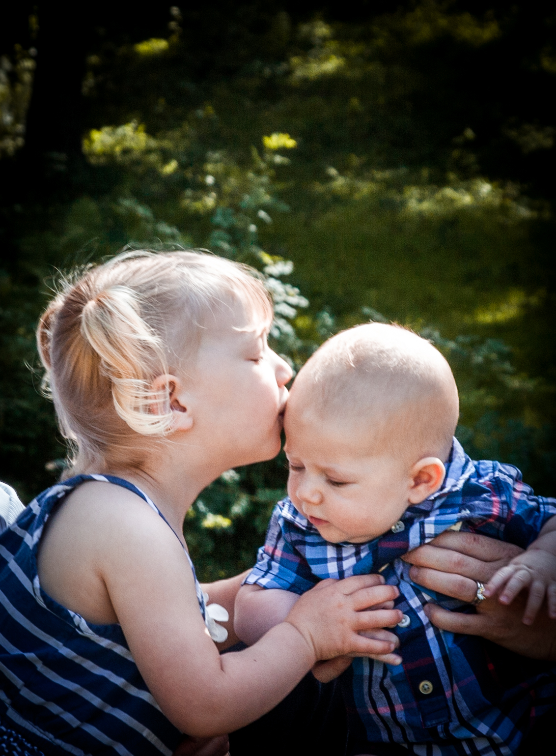 Sister kissing baby brother