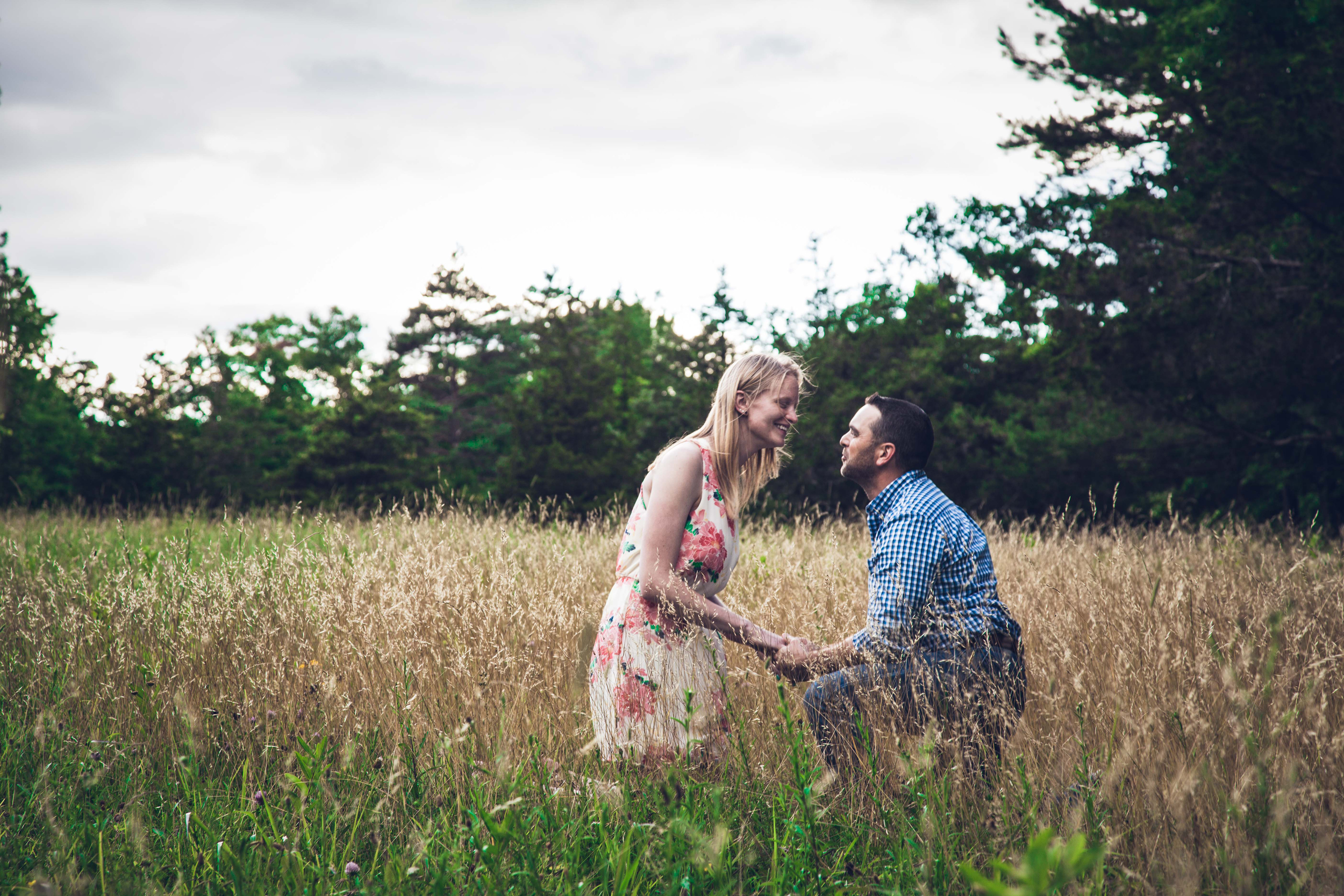 couple in the grass field proposing
