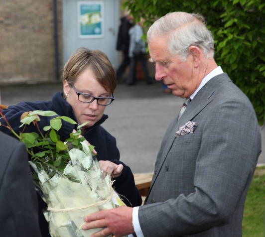 Lucy Simpson, manager at Poundbury Gardens, presents HRH The Prince of Wales with an old fashioned yellow shrub rose, named Charlotte. Picture courtesy of Neil Crick ARPS.