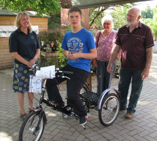 From left to right, Louise Burks, managing director of The Gardens Group, Callum Watson on his new tricycle, Pauline Eke and John Eke.