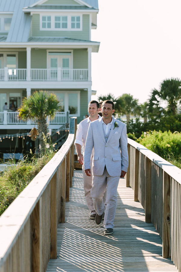 Groom in tan suit before beach wedding by One Life Photography