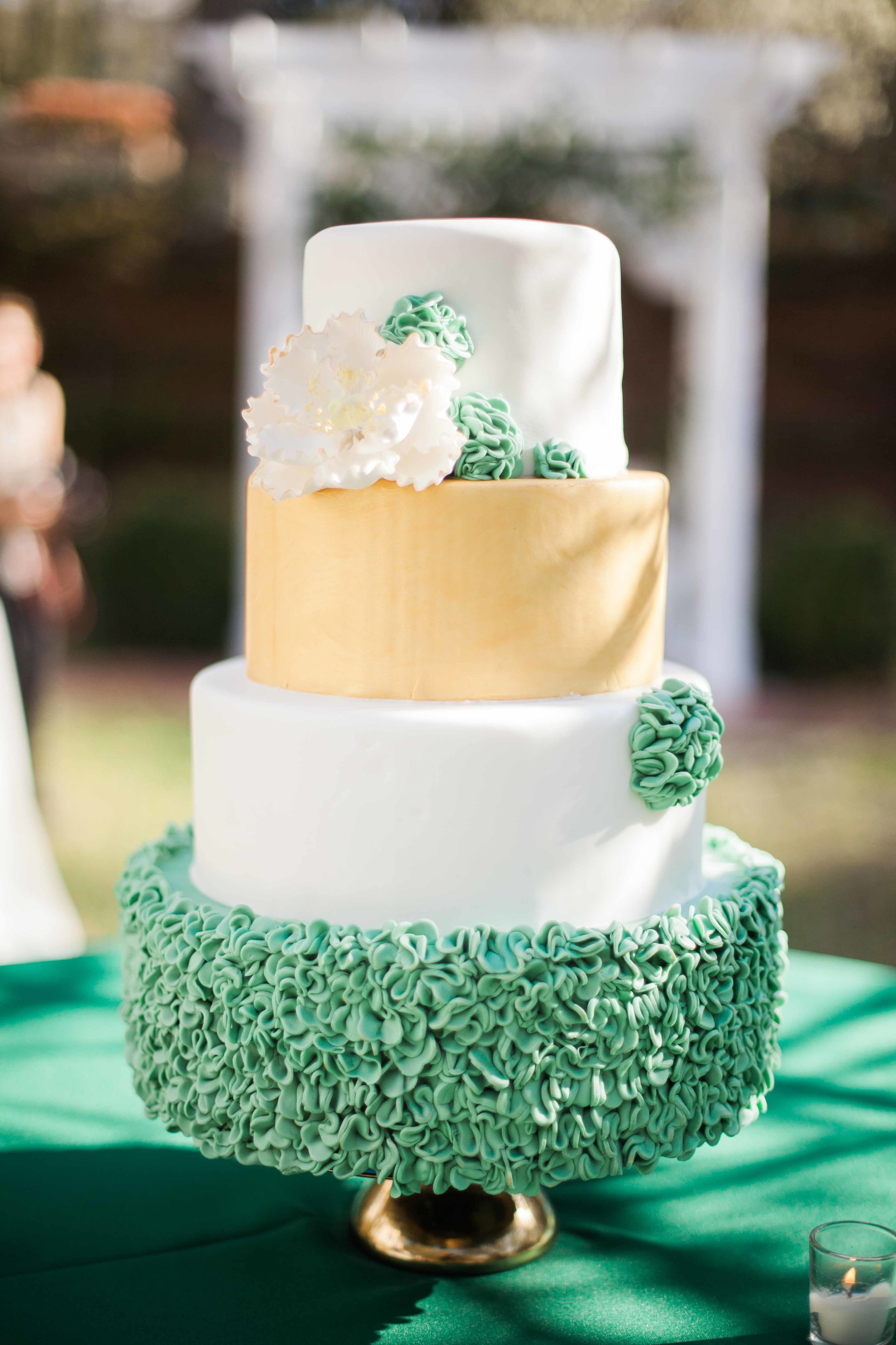 Four tiered green and gold cake with ruffled detailing by Creative Cake Design at Burgwin-Wright House