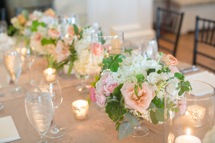 White hydrangeas, peach roses and ranunculus centerpieces by Sara York Grimshaw Designs at Rebecca + Christian's Kiawah Island River Course wedding photographed by Captured by Kate Photography.