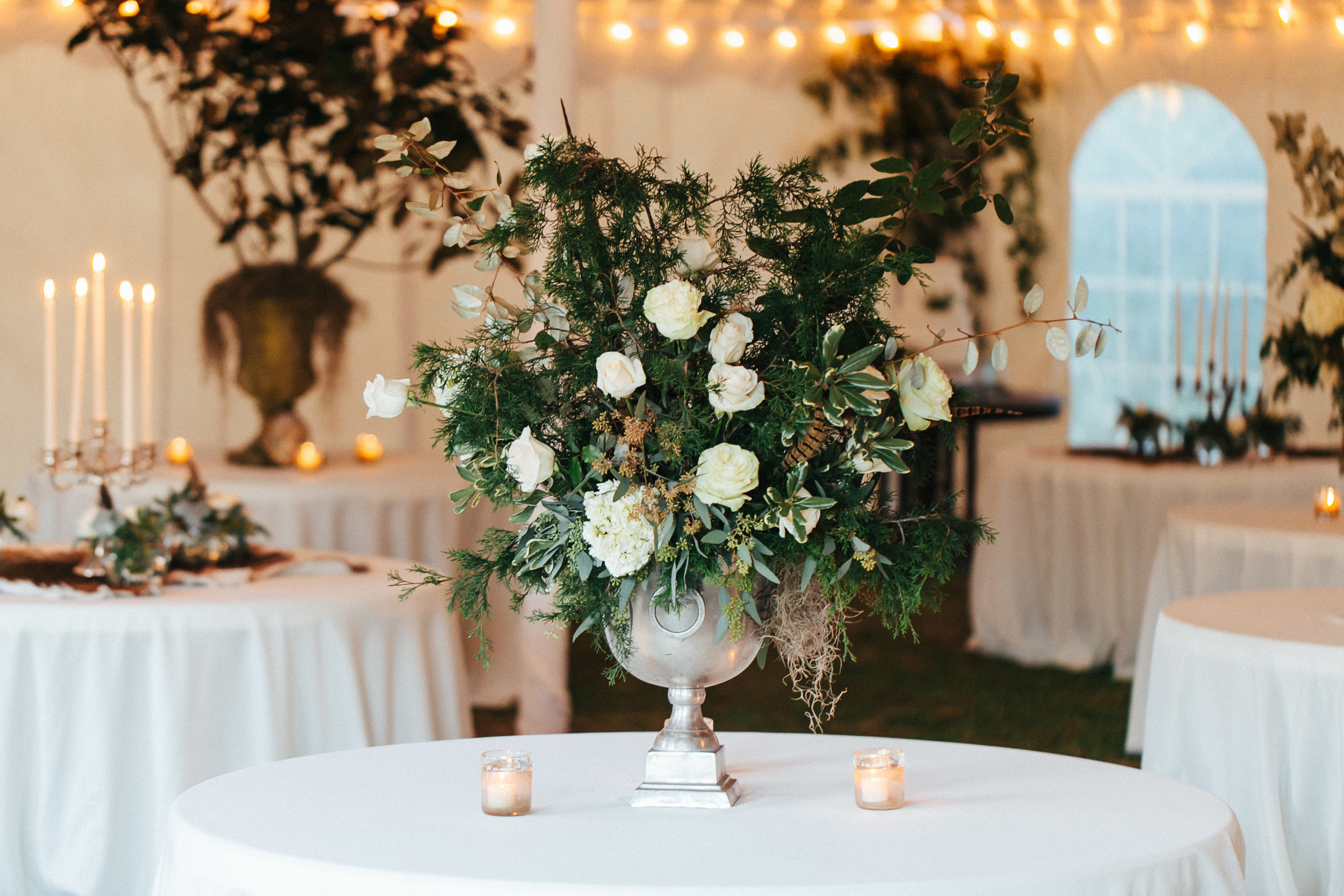 Lush centerpieces of white roses, hydrangeas, spanish moss and pheasant feathers