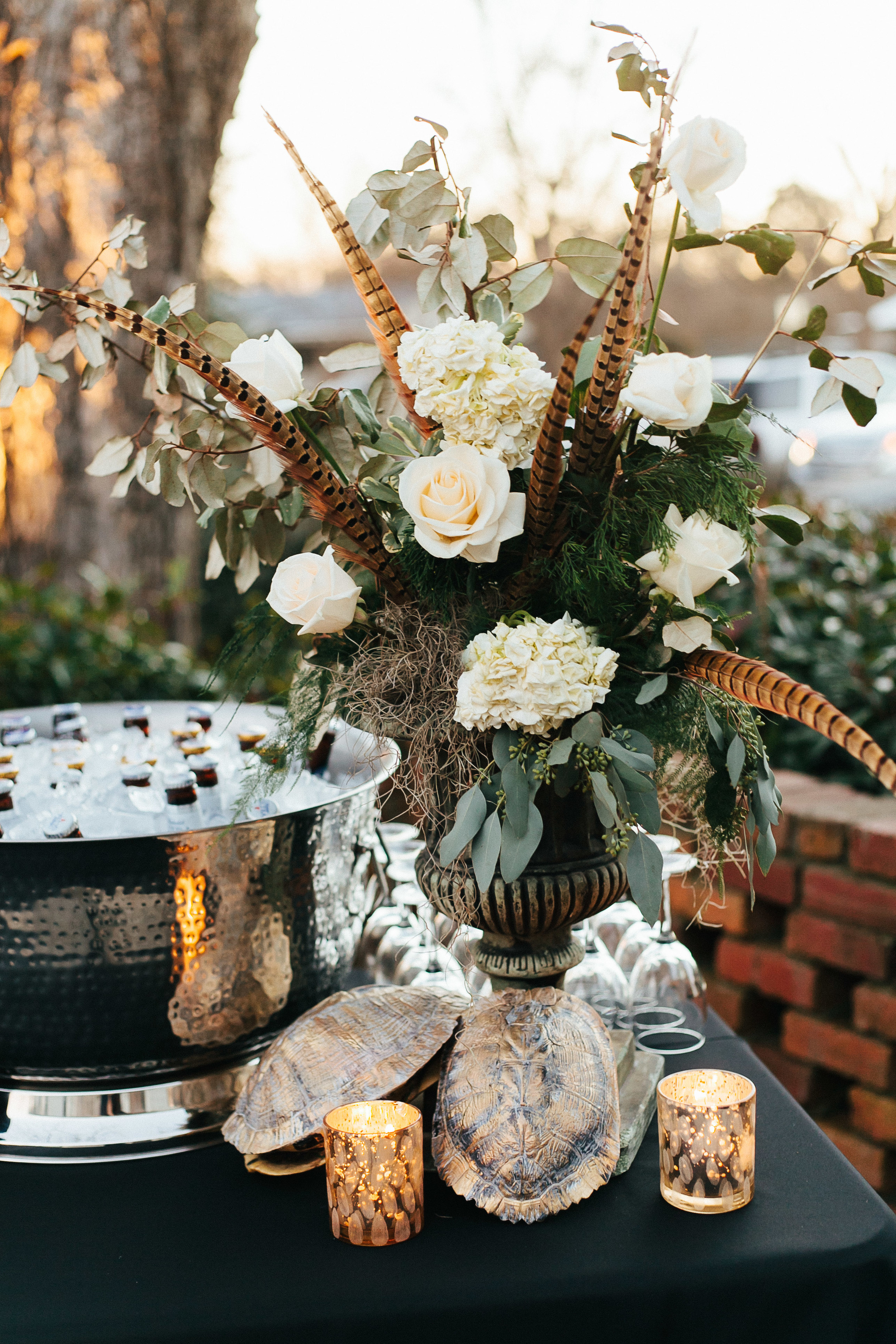 Lush centerpieces of white roses, hydrangeas, spanish moss and pheasant feathers with trutle shells