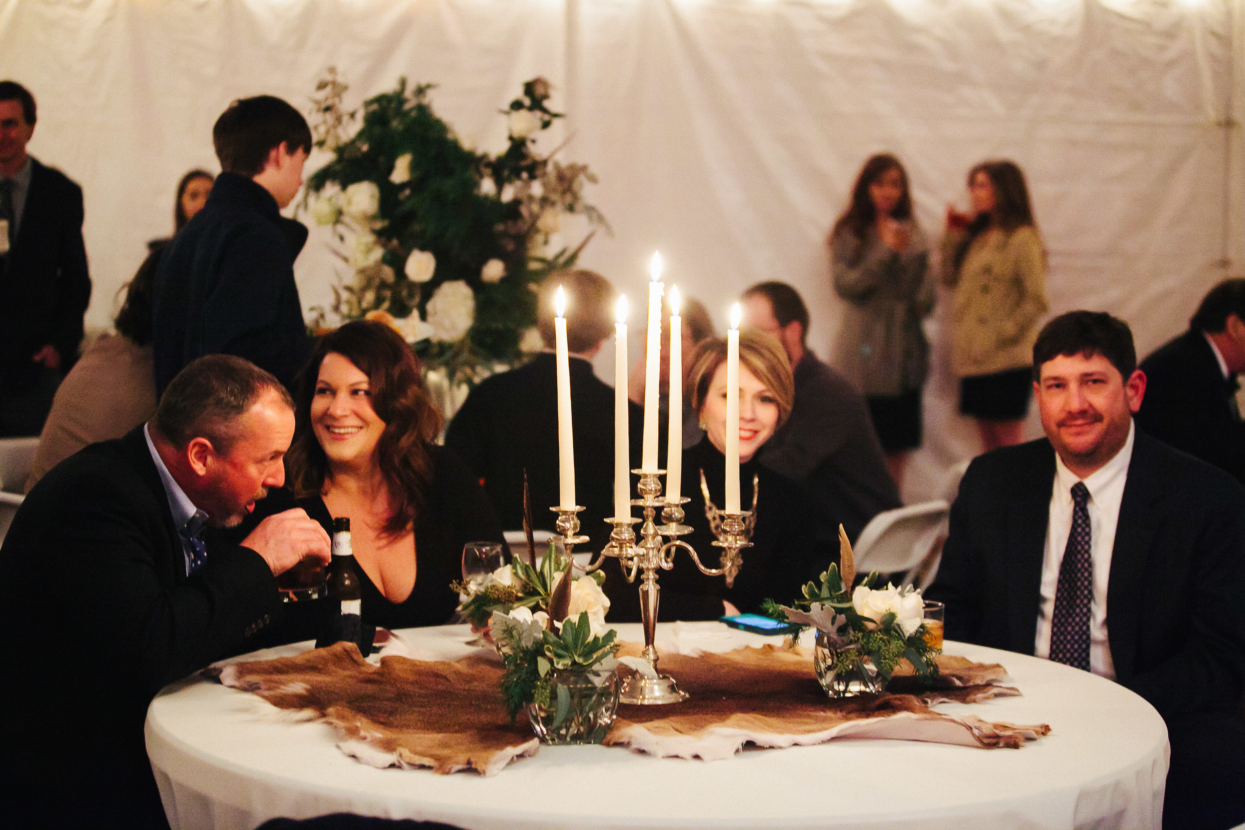 Lush centerpieces of white roses, hydrangeas, spanish moss and pheasant feathers, turtle shells, animal fur table runners and antique candelabras