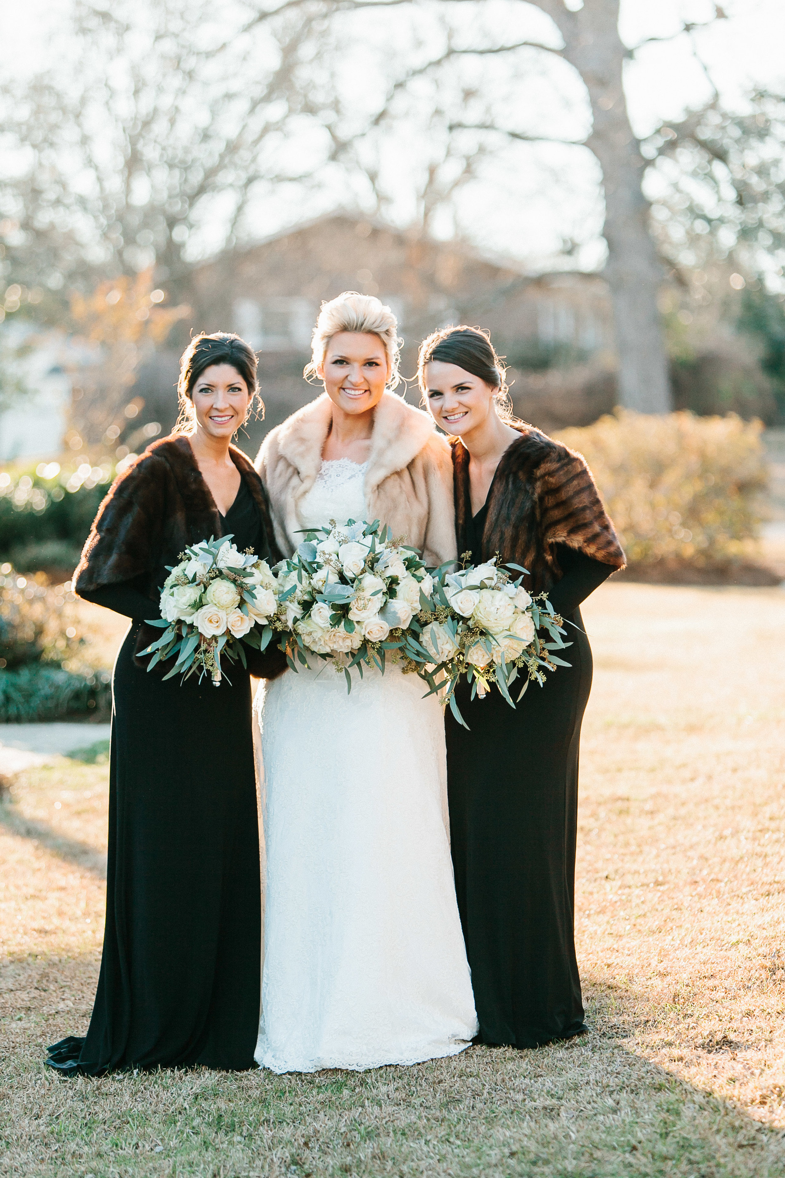 Long-sleeved black bridesmaids dresses with fur stoles for Rustic Winter Woodland wedding by Mark Williams Studio.