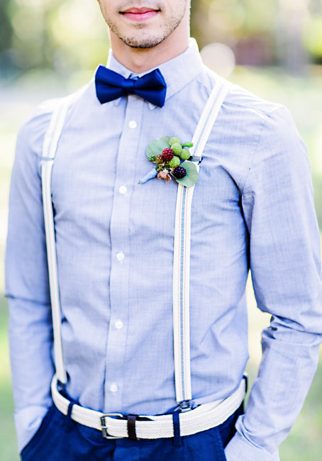 Groom wearing a bow tie, berry boutonniere and suspenders at rustic elopement