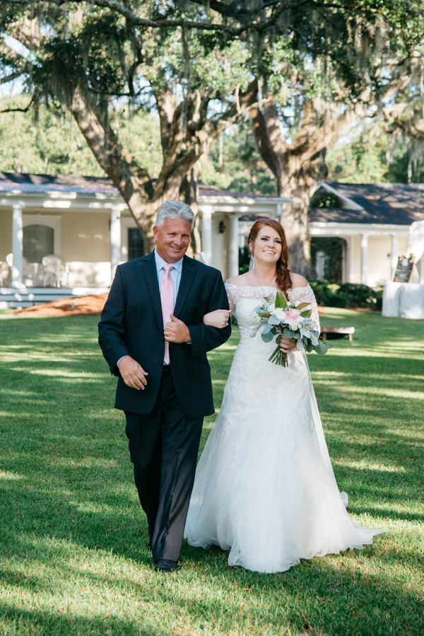 Father walking daughter down the aisle at outdoor wedding ceremony in Charleston, Sc