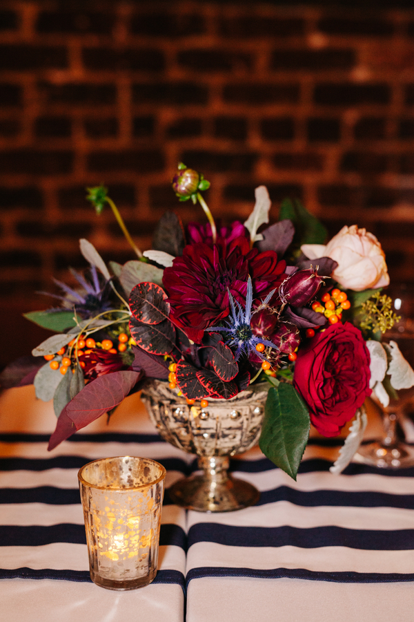 Deep red centerpieces and black and white striped linens at Charleston wedding