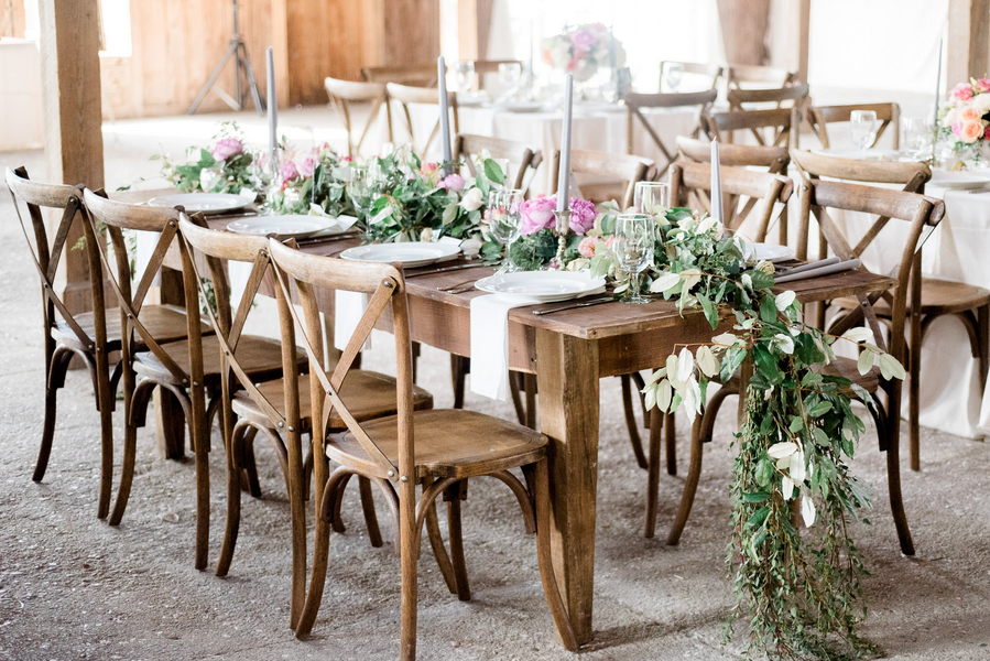 Rustic reception with candles and greenery by Charleston Stems