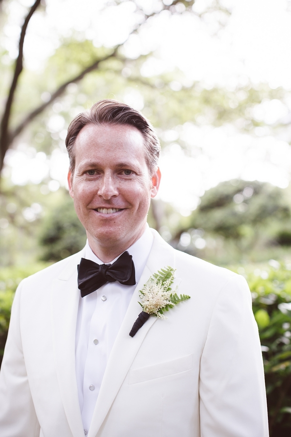 Groom in a white dinner jacket and black bow tie