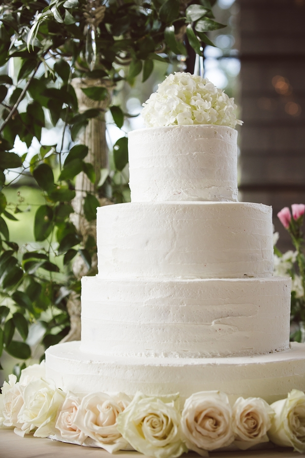 Four-tiered, simple white cake with floral topper