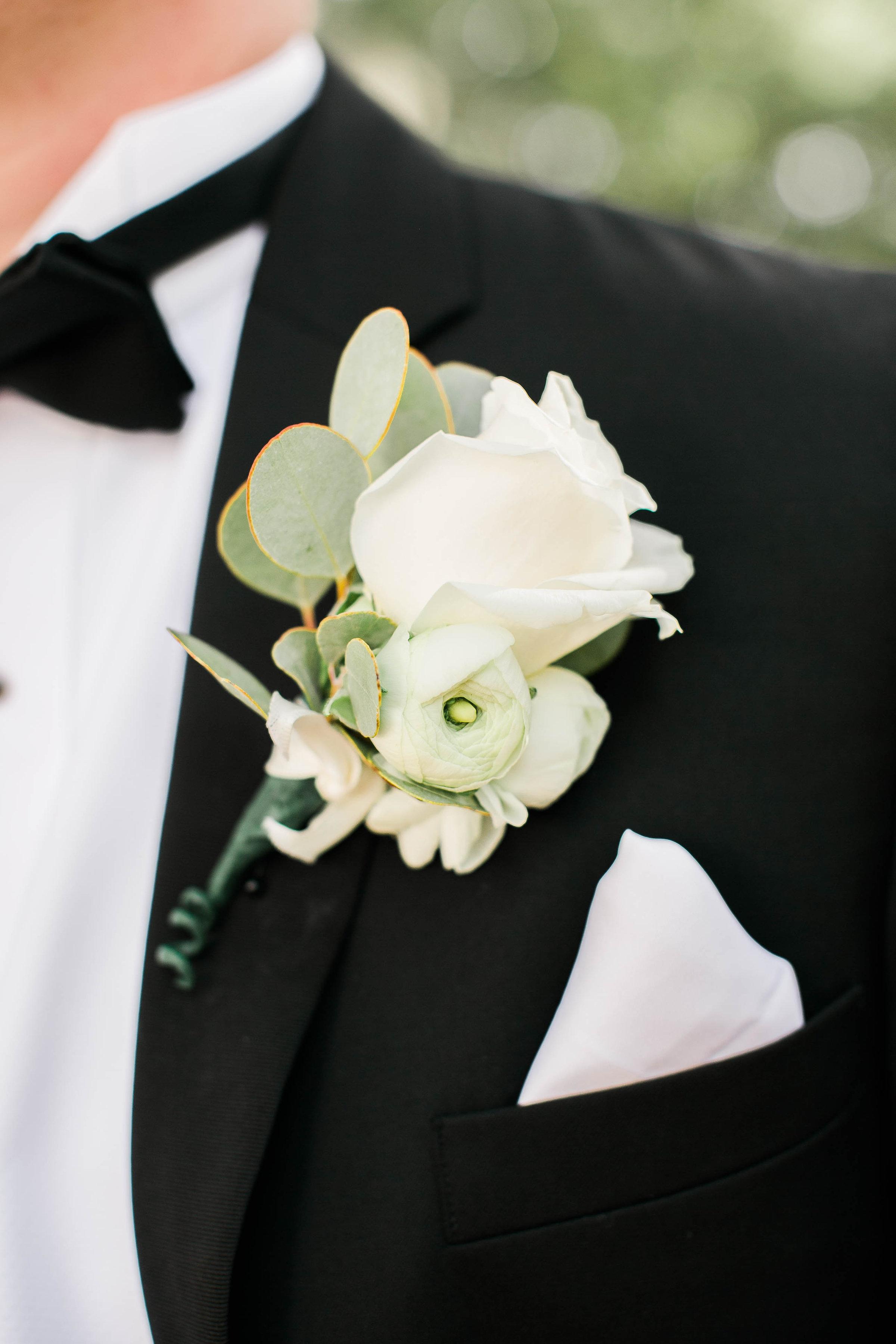 White rose boutonniere on a black tuxedo