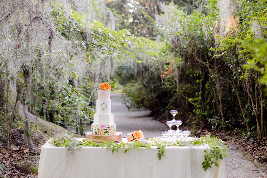 Four-tiered wedding cake by Sweet Rhi with champagne tower