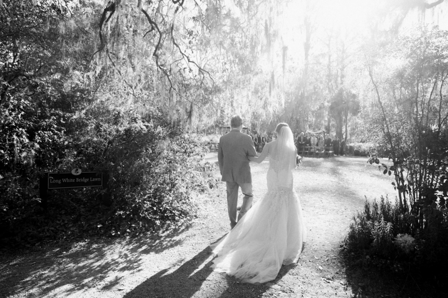 Father of the bride walking his daughter down the aisle at Magnolia Plantation outdoor wedding // Black and white Charleston wedding photography on A Lowcountry Wedding Magazine