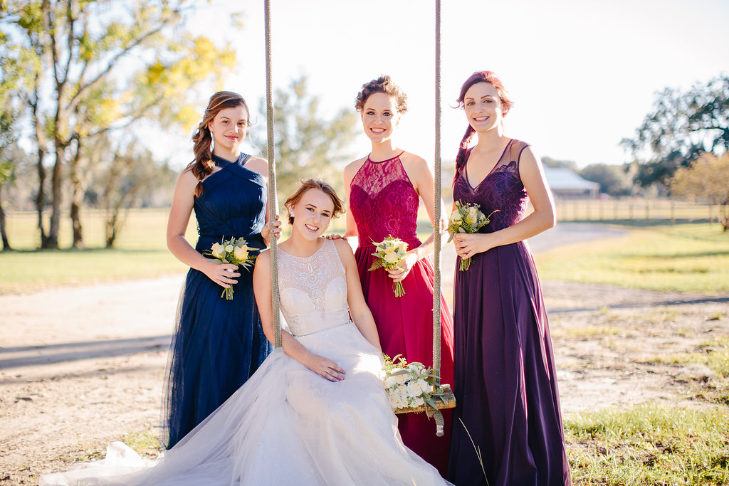 Bride on a swing at Sugah Cain Plantation with her bridesmaids on Johns Island, SC //  Charleston wedding photography by Carolina Photosmith  // Bride and her maids at Sugah Cain Plantation in front of white horse and Carriage  //  on A Lowocountry Wedding Magazine & Blog