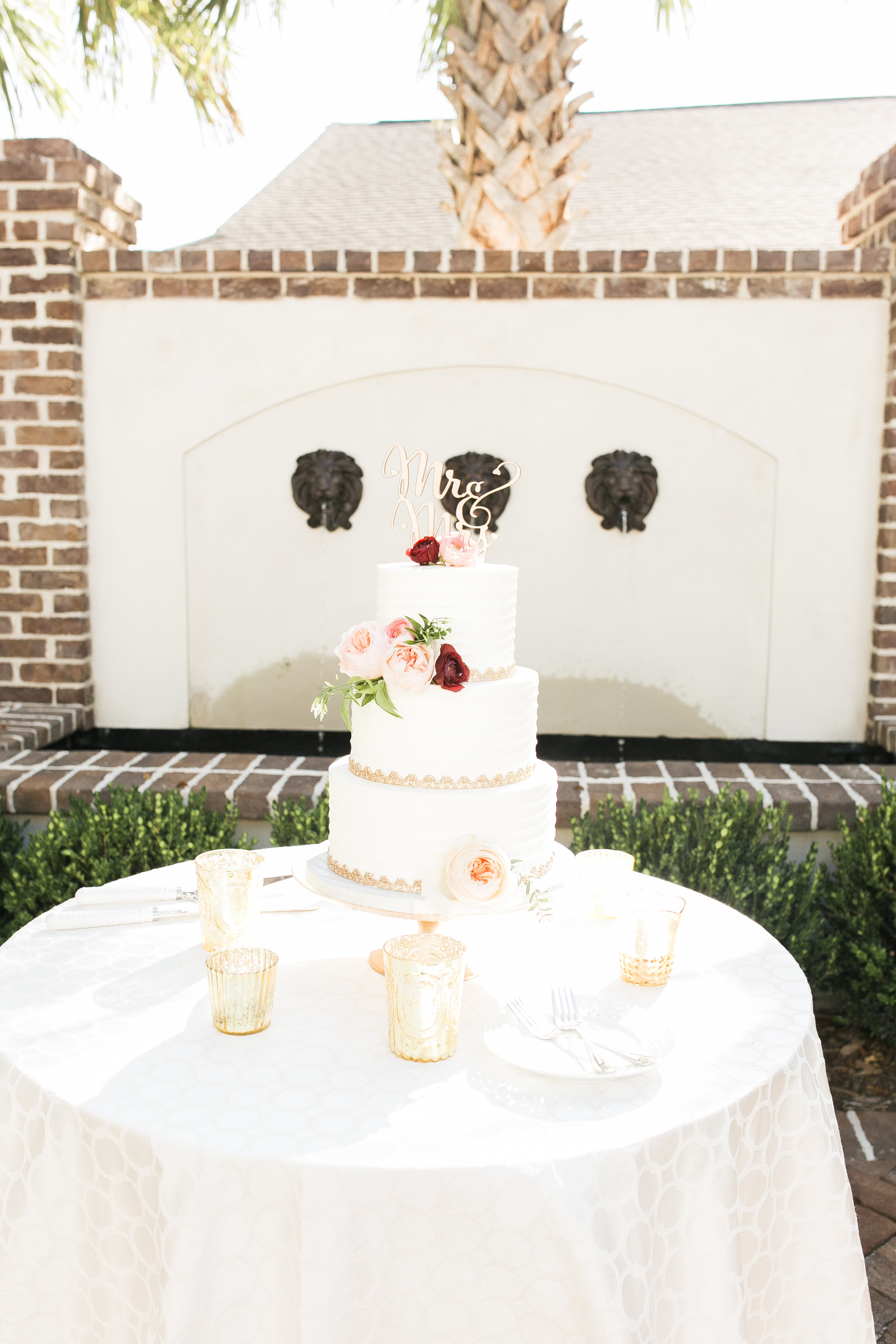 Four-tiered white cake with gold trim at Thomas Bennett House weddingg  Colorful outdoor reception at The Thomas Bennett House wedding in Charleston, SC  //  photographed by Jenna Weddings  Traditional wedding ceremony at Cathedral of St. John the Baptist in Charleston, SC  //  A Lowcountry Wedding Magazine & Blog