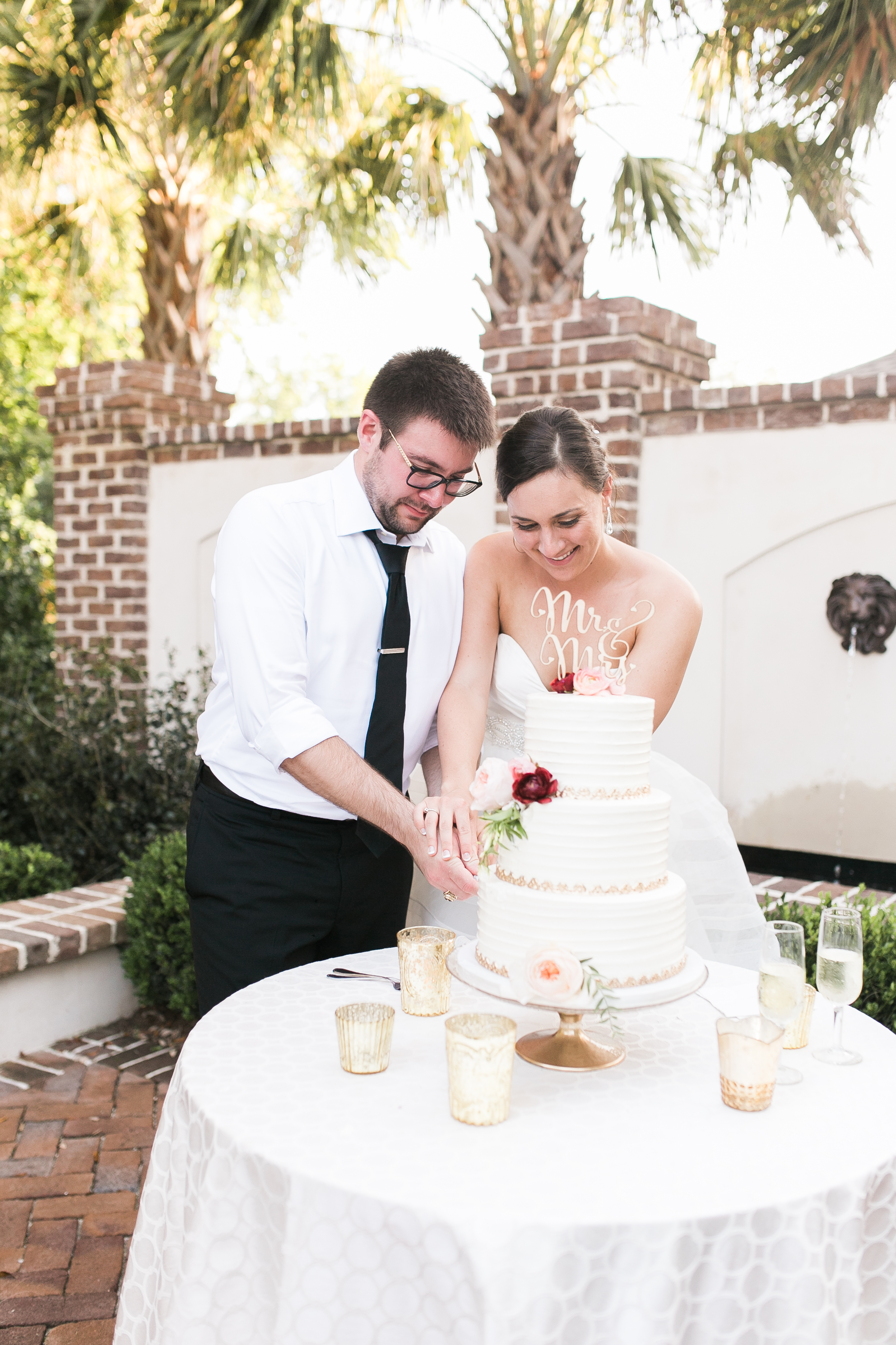 Bride & Groom cutting the cake at Charleston, SC wedding  Colorful outdoor reception at The Thomas Bennett House wedding in Charleston, SC  //  photographed by Jenna Weddings  Traditional wedding ceremony at Cathedral of St. John the Baptist in Charleston, SC  //  A Lowcountry Wedding Magazine & Blog